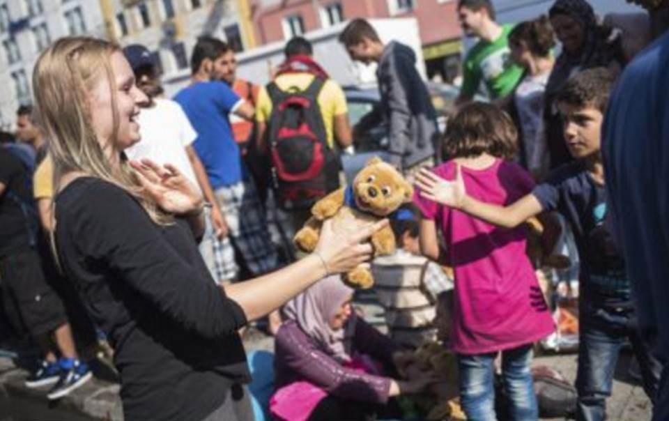 Una trabajadora de 'Ayuda a los Refugiados en Múnich' con un niño. / EFE